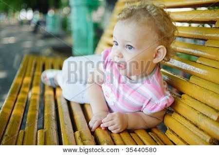 Cute Curly Haired Baby Girl On Bench