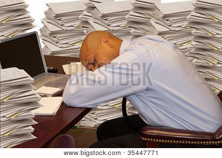 Man Sleeping At Desk With Stacks Of Paperwork