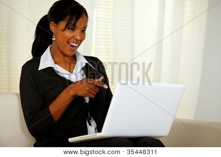 Smiling Woman On Black Suit Pointing To Laptop
