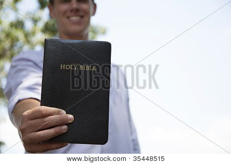 Jovem prende a Bíblia e sorrisos