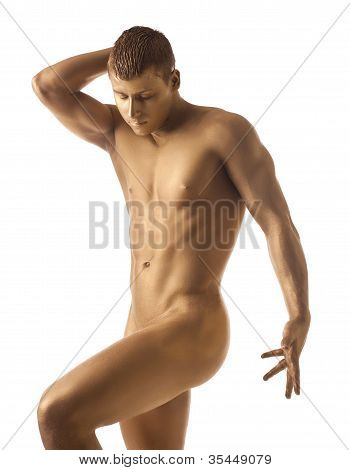 Strong athletic man posing nude with gold skin