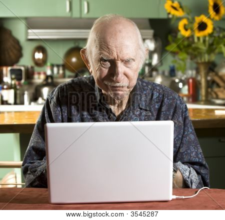 Grumpy Senior Man With A Laptop Computer