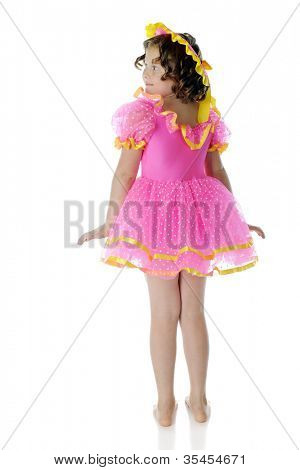 A rear view of an elementary child with ringlets, wearing a frilly pink dress and hat with yellow trim.  On a white background.
