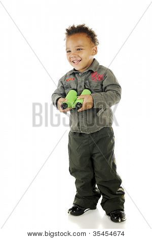 An adorable preschooler wearing Air Force garb happily holding a pair of binoculars.  On a white background.