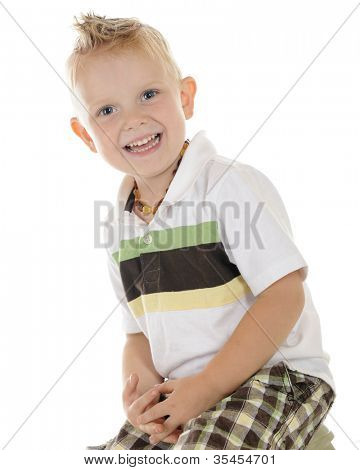 An adorable blond preschooler happily sitting on a small stool with his hands in his lap.  On a white background.