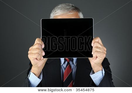 Closeup of a businessman holding his tablet computer with blank screen in front of his face.. Horizontal format over a light to dark gray background. Man is unrecognizable.