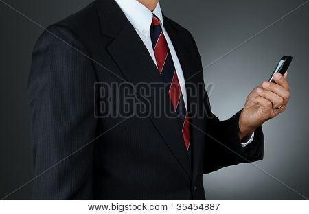 Closeup of a businessman checking messages on his cell phone. Horizontal format over a light to dark gray background. Man is unrecognizable.