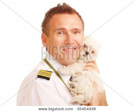 Airline pilot wearing uniform with epaulettes with little puppy, dog breed is Maltese. Good photo to illustrate pet friendly airlines.
