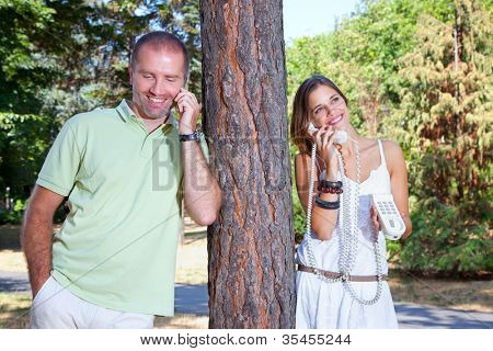Young beautiful  couple man and woman talking by phone in park. Summer set