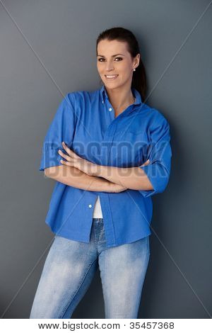 Portrait of smiling woman standing at wall with arms crossed, looking at camera.