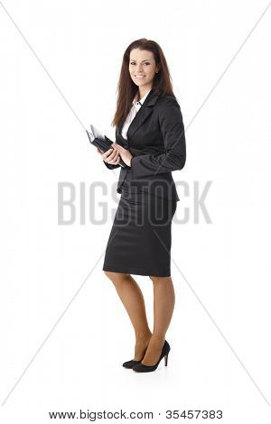 Smiling elegant pretty businesswoman standing with personal calendar handheld, looking at camera.
