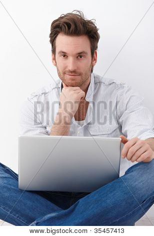 Handsome young man sitting in tailor seat on floor, using laptop, smiling.