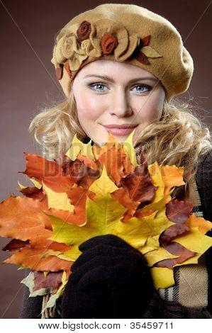 Mujer joven con el otoño las hojas en la mano