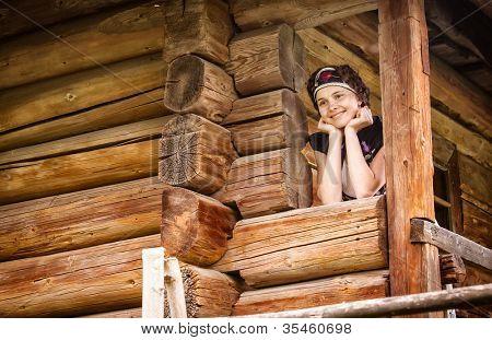 Chica húngara en ropa nacional en la casa de madera