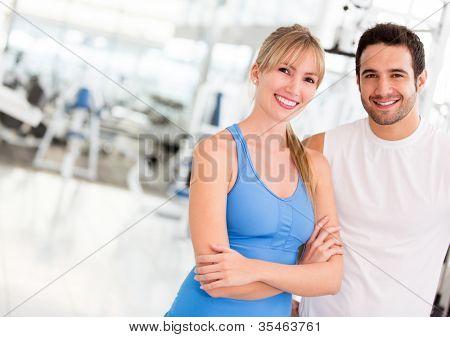 Atractiva pareja en el gimnasio mirando feliz