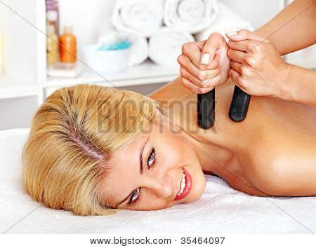Satisfied woman getting massage in health resort.