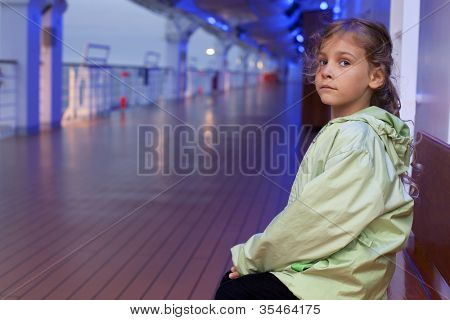 Little girl sitting on bench on deck of large passenger ship