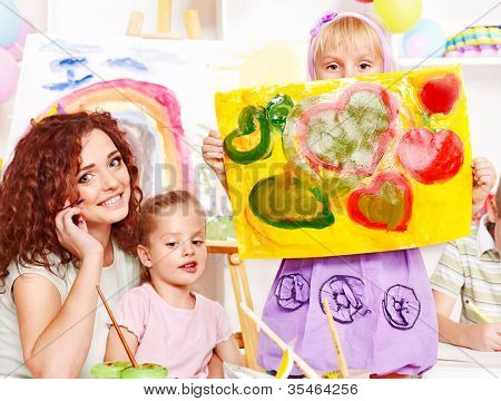Child girl and teacher painting  in school.