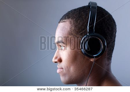 Profile of a african man listening to music on grey background