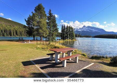 A lovely spot for a picnic by the lake - a wooden table and bench. Quiet shallow lake in Banff National Park in Canada. Sunset