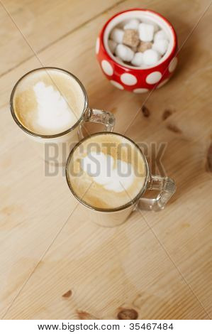 coffee latte in two tall glasses and sugar bowl, shallow dof