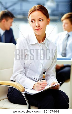 Pretty business woman with dreamy look making notes white at office
