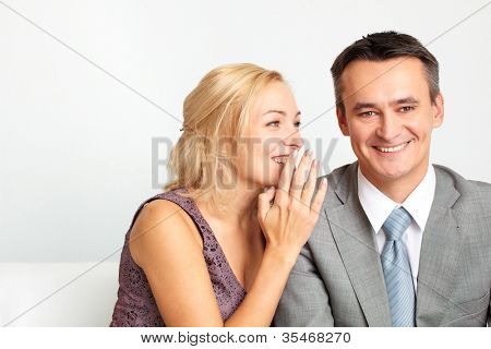 Cheerful woman whispering something funny in her husband�¢�?�?s ear