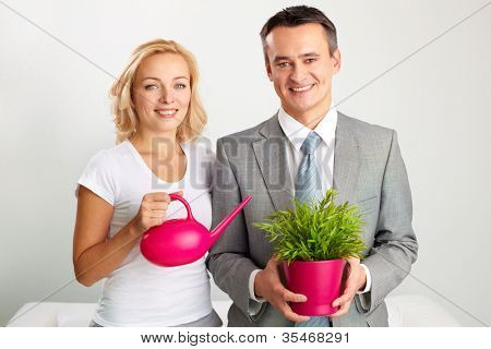 Portrait of happy gardeners holding a watering-pot and a plant