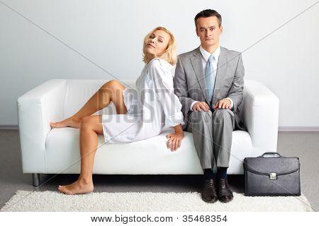 Embarrassed businessman sitting too close to a sensual woman in loose clothes