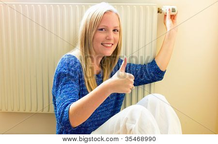 a young woman sits in front of a radiator in the winter.