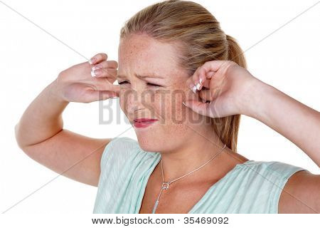 a young woman holds her fingers in her ears. loudness and tinnitus.,