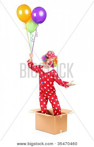 Clown holding balloons and standing in a cardboard box, isolated on white background
