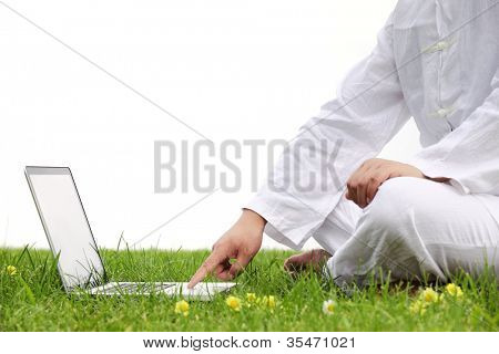 Man using Laptop on meadow,Closeup.