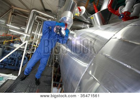 Technician in mask, gloves, goggles and blue uniform reparing technological system