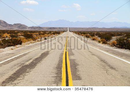 Long desert highway leading into Mojave Desert
