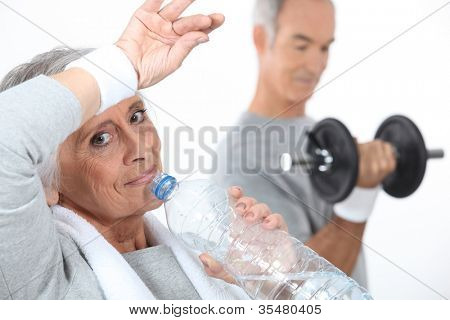 Elderly woman drinking water after gym session