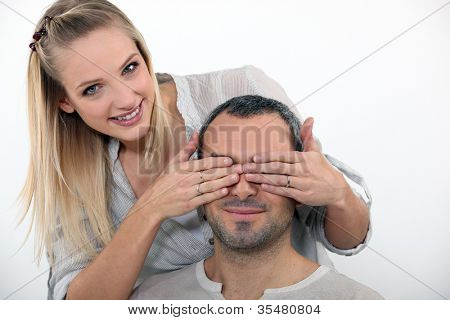 Young woman covering her husband's eyes
