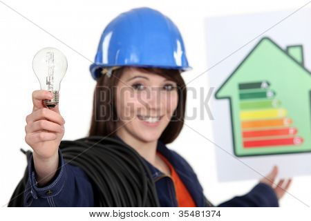 Woman holding energy rating poster and light bulb