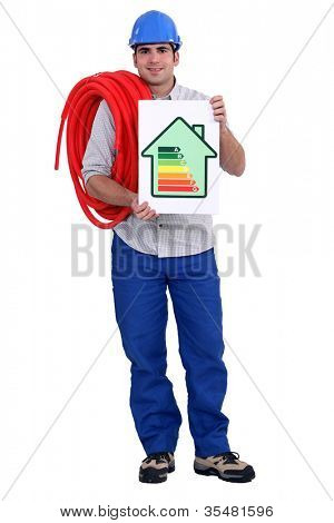 Man holding length of pipe and energy rating poster