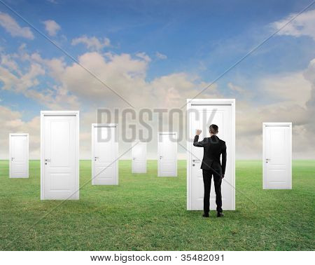 Young businessman knocking at one of many white doors on a green meadow