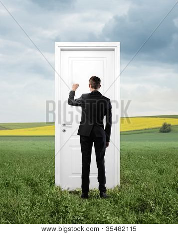Young businessman knocking at an entrance door on a green meadow