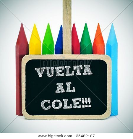 sentence back to school written in spanish, vuelta al cole, in a blackboard label and some crayons of different colors in the background