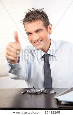 Businessman showing thumb up at work in office.