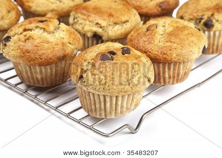 Homemade banana chocolate chip muffins on a wire rack.