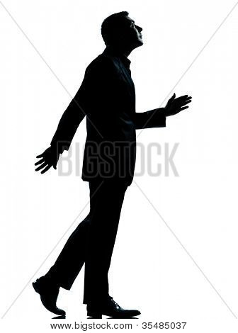 one caucasian business man walking looking up silhouette Full length in studio isolated on white background