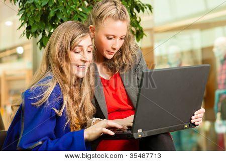 Zwei Freundinnen gehen zusammen Einkaufen und haben eine Menge SpaÃ??Ã?? beim Shoppen in einer Mall, sie haben ein Laptop gekauft