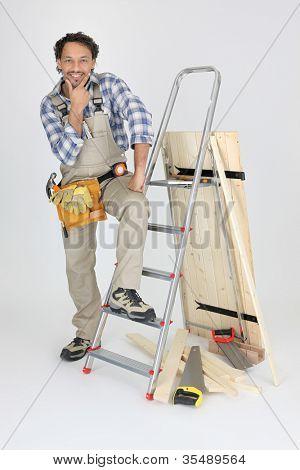 portrait of cabinetmaker posing near ladder