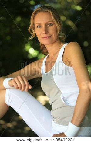Blond woman stretching before jogging