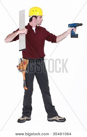 Tradesman holding a girder and a power tool