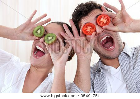 Covering his eyes with a couple slices of kiwi and tomato